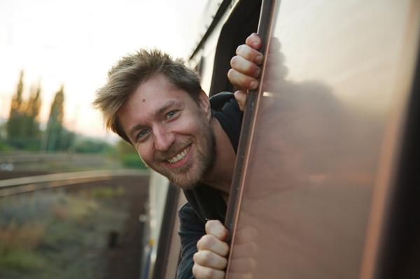 Man som kollar ut från tågfönster.