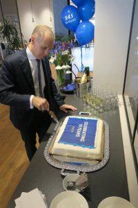 SAS koncernchef Rickard Gustafson skär upp jubileumstårtan.